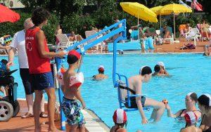 una persona entra in piscina con un sollevatore