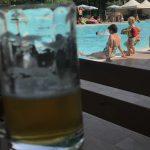 Un bicchiere di birra in primo piano e sullo sfondo persone in piscina