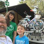 In primo piano un adulto e due bambini in secondo piano un auto carica di biciclette