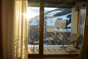 Vista dalla camera di hotel sul balcone con sdraio e panorama esterno innevato
