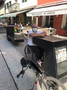 una persona in carrozzina davanti al tavolino di un bar in centro a San Candido