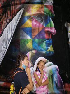 Murales con soggetto il profilo di Dante Alighieri come mosaico, due bambine sono in posa davanti al murales