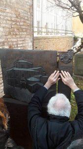 Una persona tocca una scultura a rilievo